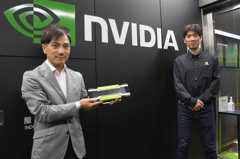 NVIDIA社名ロゴの前に立つ佐々木様と当社森