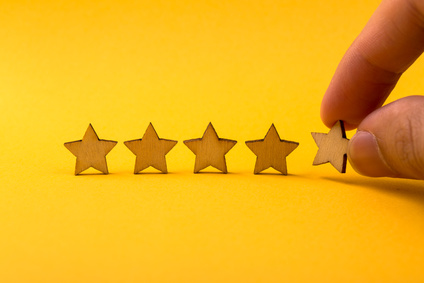 Hand putting wooden five star shape on yellow background