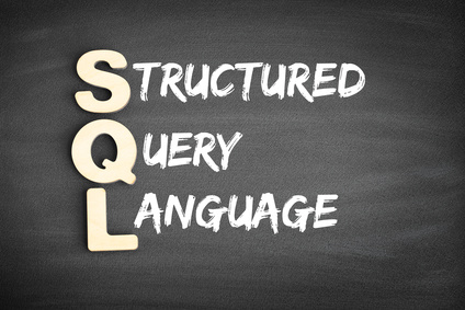 Wooden alphabets building the word SQL - Structured Query Language acronym on blackboard